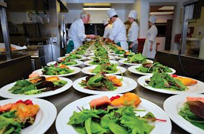 Table full of salad plates being prepared by chefs