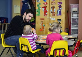Guy sitting with two children in a classroom