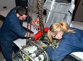Male and female student working on a plane engine