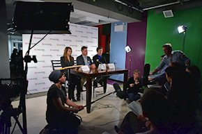 Group of students sitting at a table in front of cameras