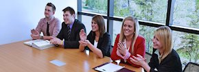 Group of professional students sitting at a table clapping