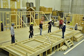 Group of carpenters building a house frame