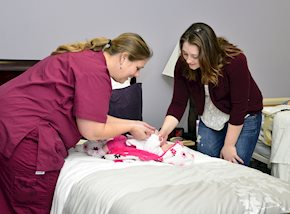 Two women changing a baby's diaper on a bed