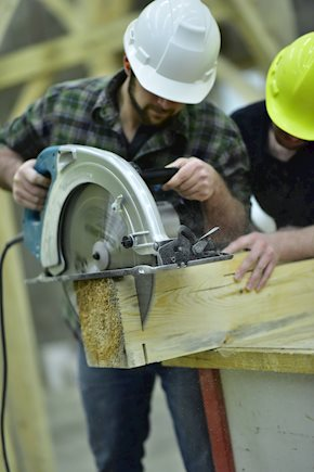 Two construction workers cutting wood with a saw