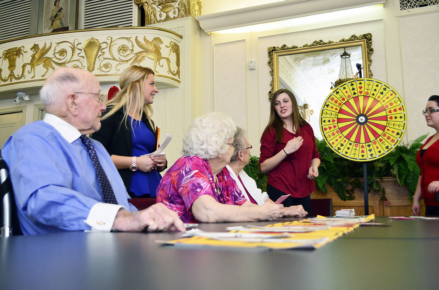 Students playing bingo with elderly people