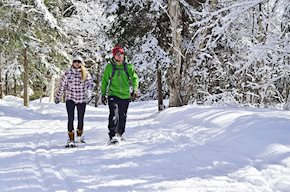 Male and female student snowshoeing in the winter