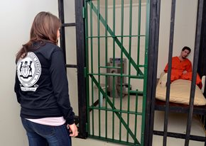 Female student looking into a jail cell