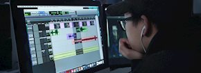 Male student looking at computer screen editing audio