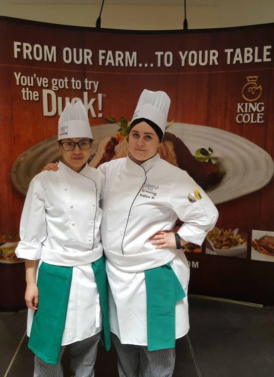 Two culinary students standing together