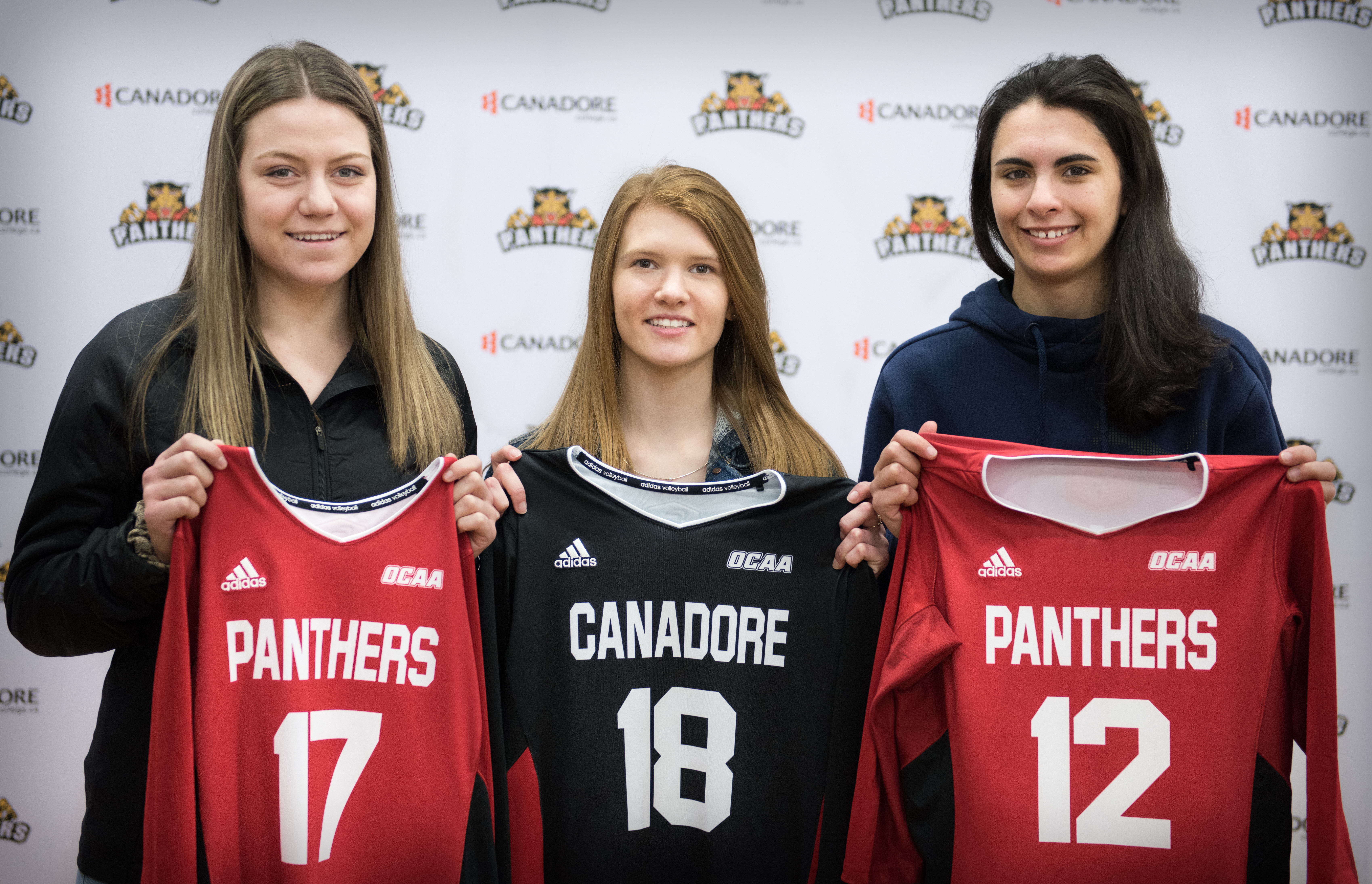 Three girls holding jerseys