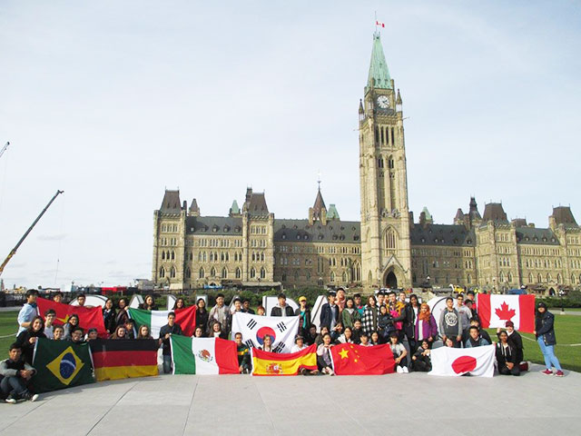 students with flags in front of the parliament building in ottawa