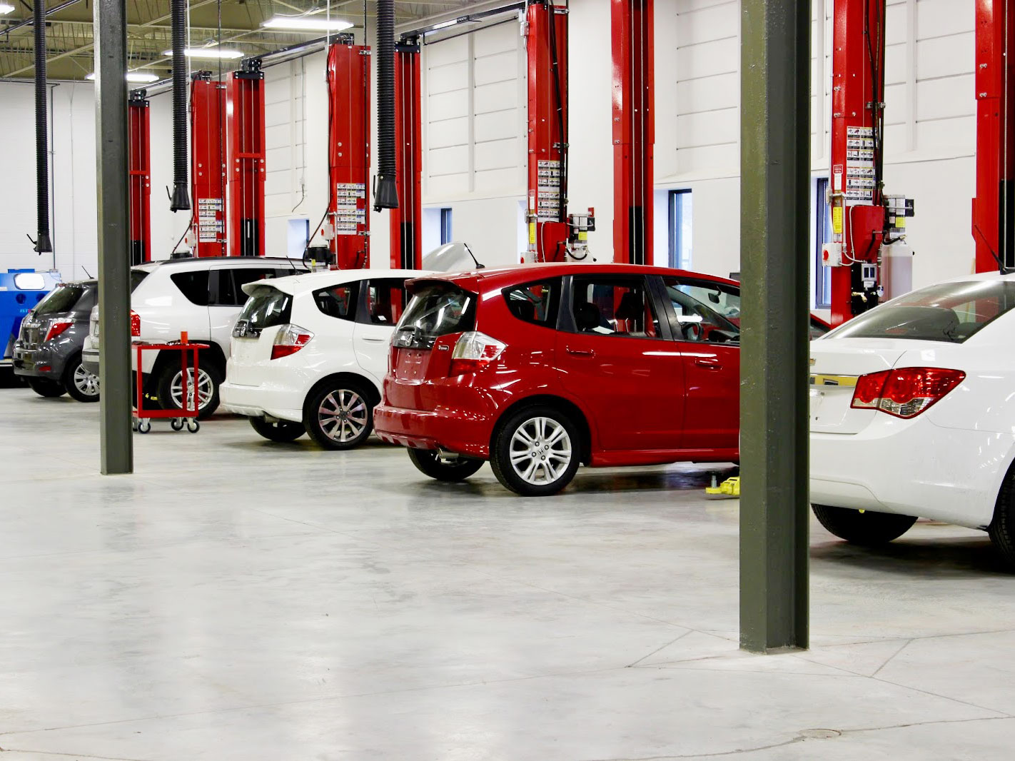 a garage with white and red cars in the parking