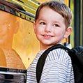 Kindergarten student standing next to a school bus