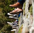 feet of teenagers sitting on mossy wall