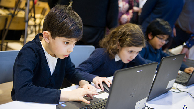 Elementary students intently coding on laptops