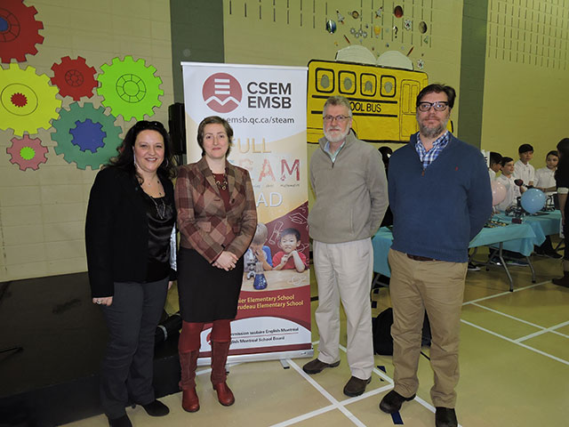 four people standing in front of a EMSB banner