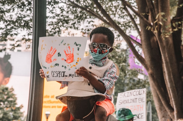 A black child holding a sign on the top of his dad's shoulders