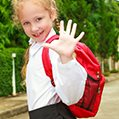 Young girl waving with backpack on
