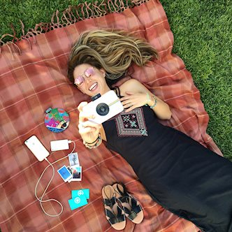 Girl on blanket enjoying Polaroid Snap camera