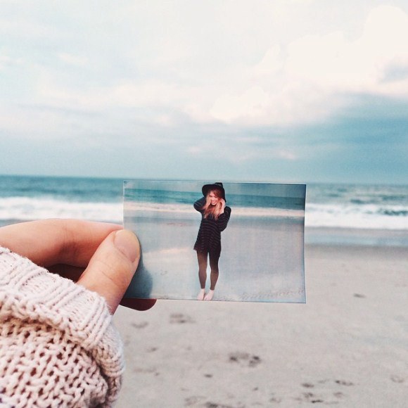 photo of girl on beach held in front of where it was taken