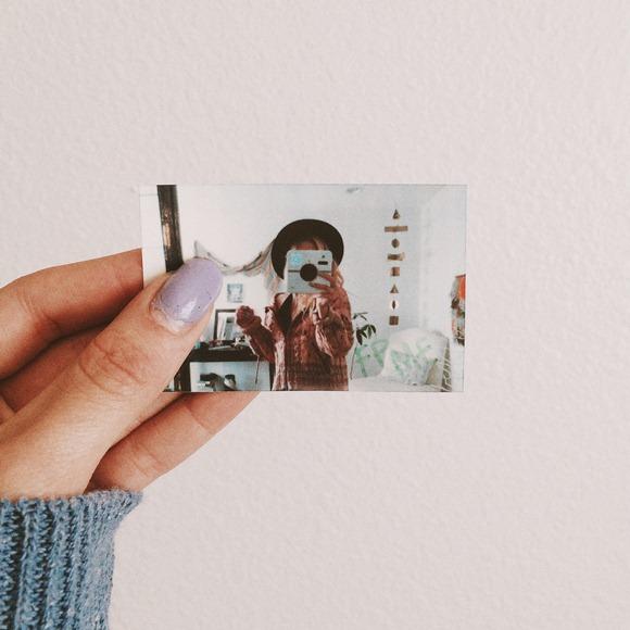 photo of girl using Polaroid camera