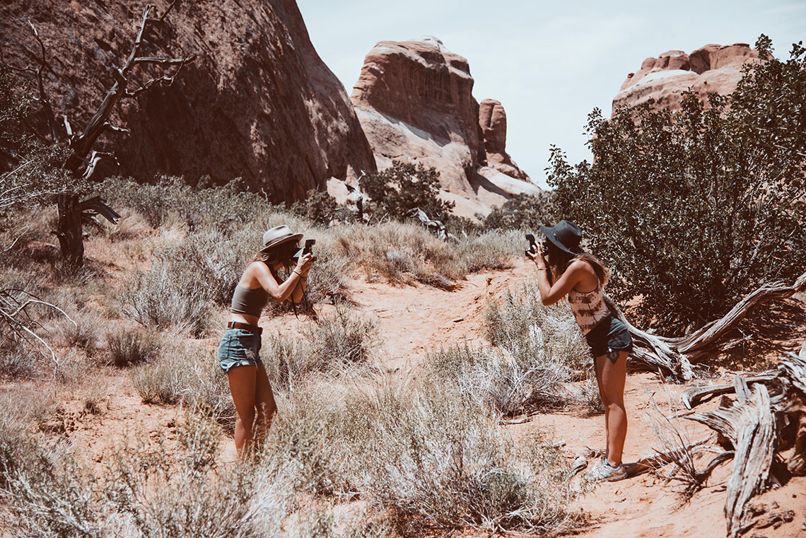 two girls taking pictures of each other with Polaroid cameras