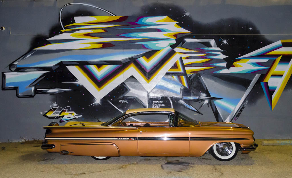 classic car in front of mural