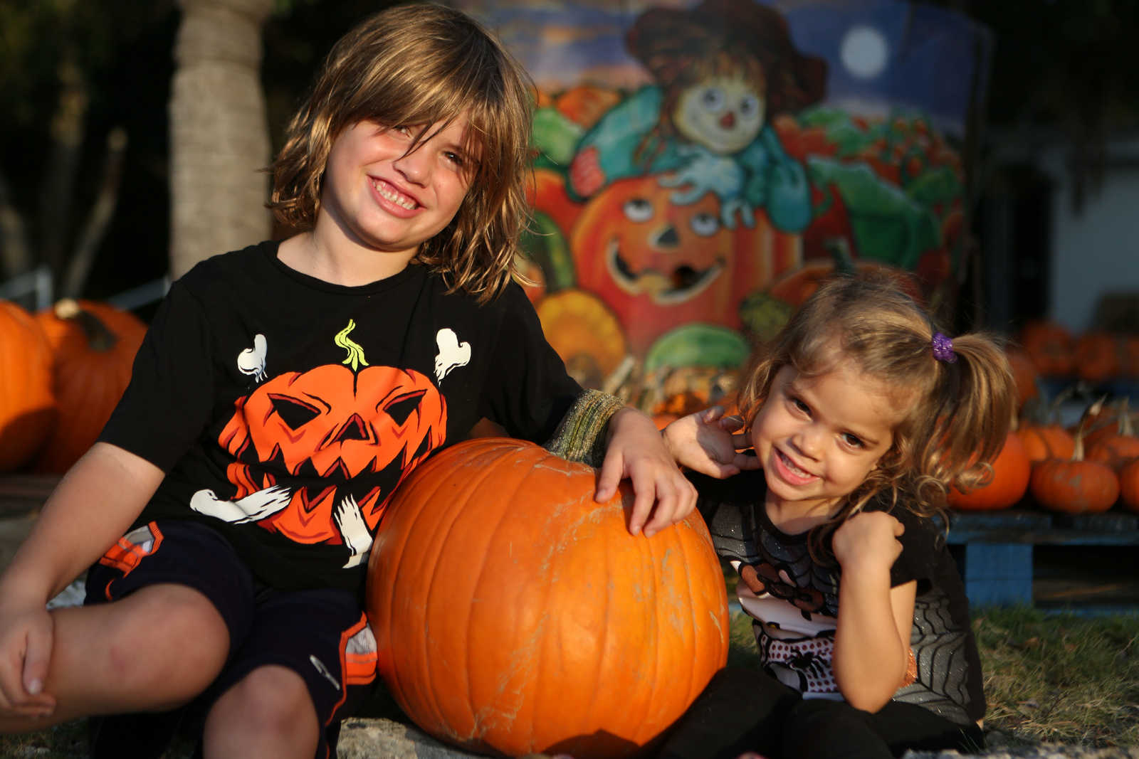 A boy and a girl posing by a large pumpkin