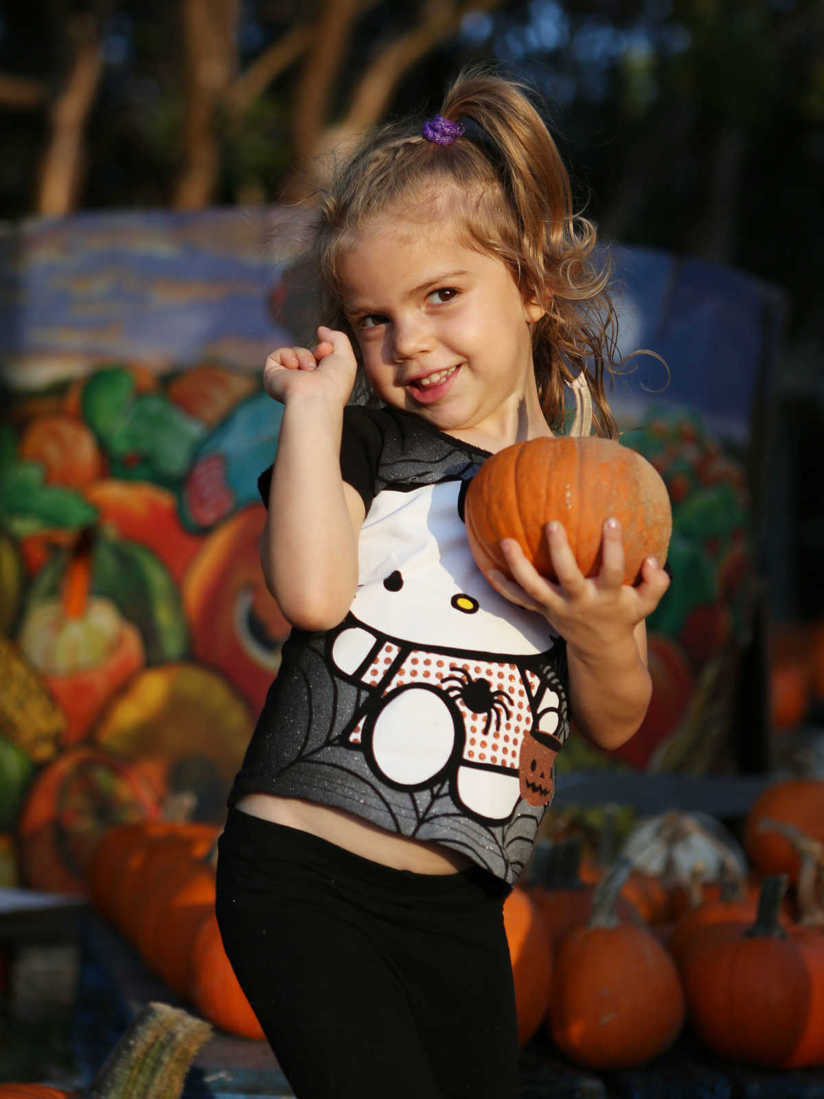 Young girl wearing a Hello Kitty shirt holding a pumpkin at a pumpkin patch