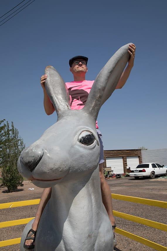 Photo of Matthew Dickey on a giant kitschy jack rabbit sculpture