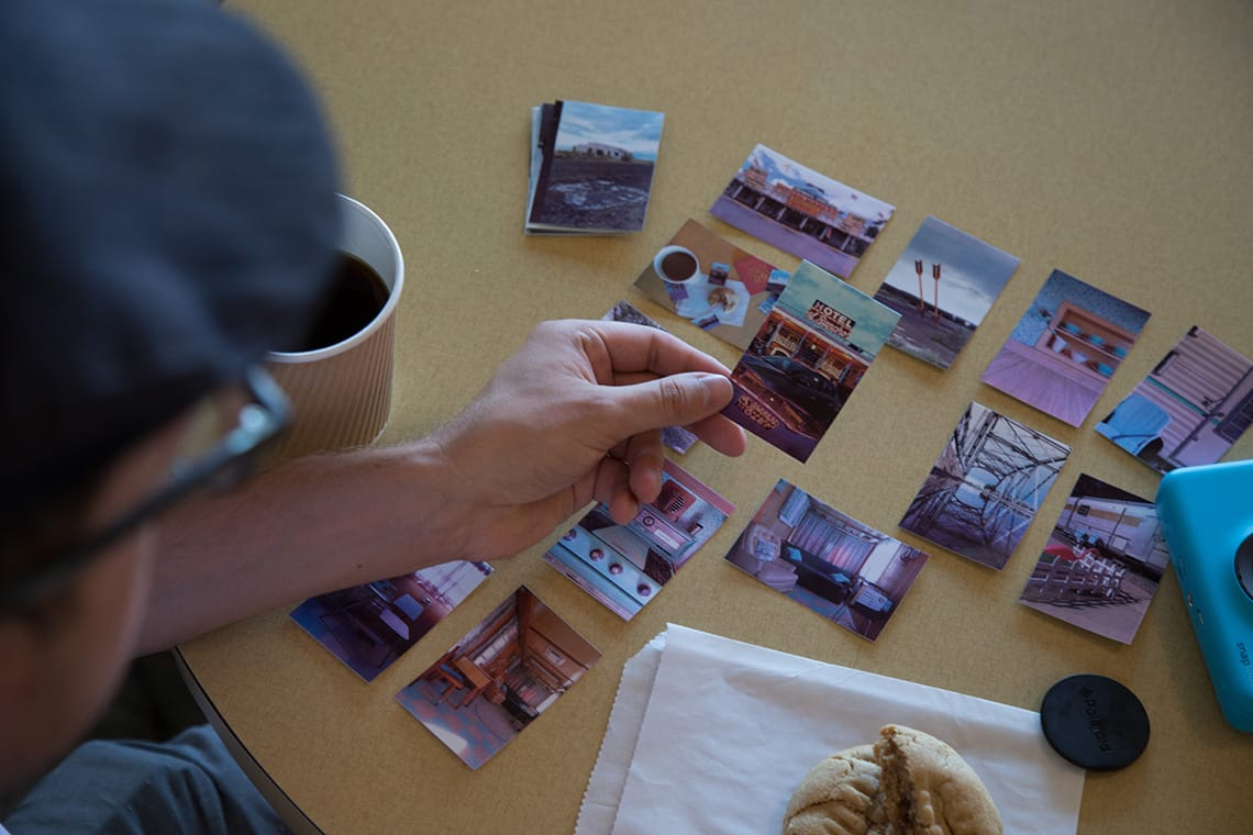 Photo of Matthew Dickey organizing a flatlay of Polaroid photos