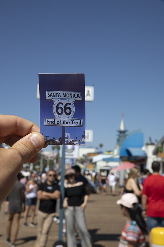 Author holding a printed Polaroid photo of Route 66 signage in Santa Monica over the orignal sign