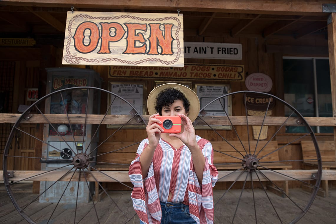 Author holding her Polaroid Snap Touch instant digital camera and standing in front of a historic store on Route 66