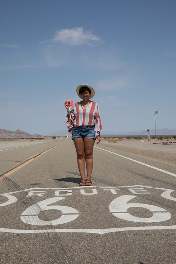 Author holding her Polaroid Snap Touch instant digital camera while standing on Route 66