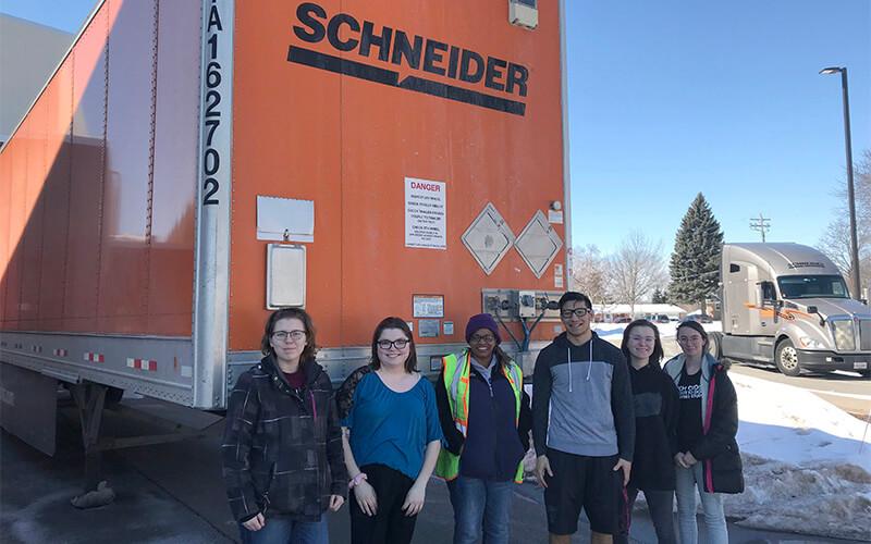 High school band stands in front of Schneider trailer