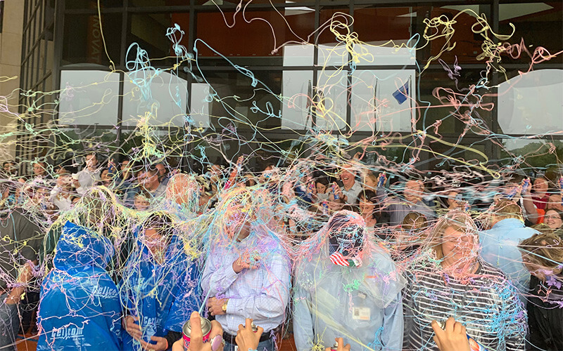 Schneider associates are sprayed with silly string for a good cause.