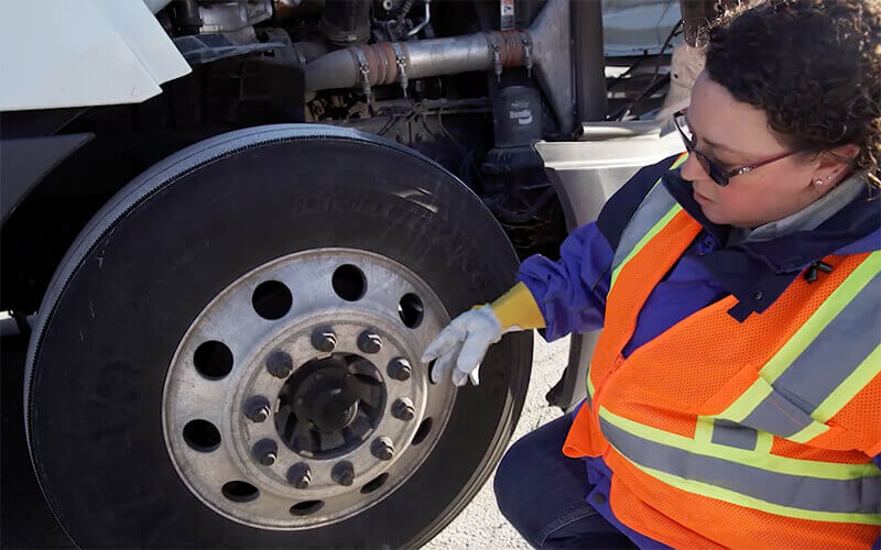 Schneider Driver Instructor Dana performs a CDL pre-trip inspection on front wheel.