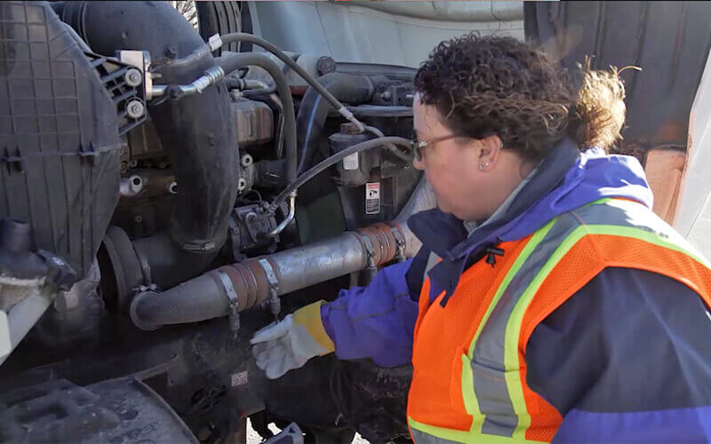 Schneider Driver Instructor Dana performs a CDL pre-trip inspection on passenger side of engine.