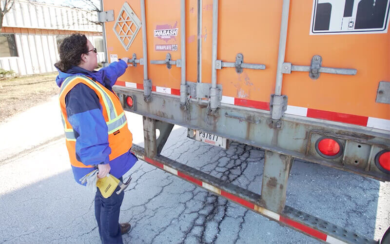 Schneider Driver Instructor Dana performs a CDL pre-trip inspection on rear of trailer.