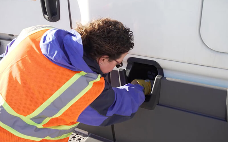 Schneider Driver Instructor Dana performs a CDL pre-trip inspection on side of cab.