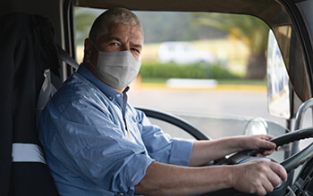 Truck driver in cab wearing a mask