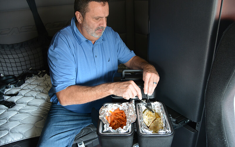 Truck driver cooking in a semi truck