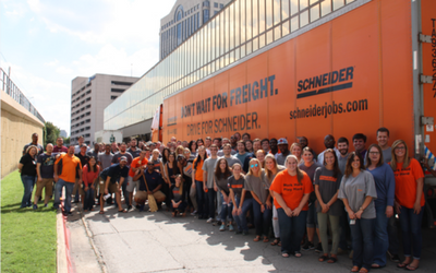 Schneider associates in front of trailer.