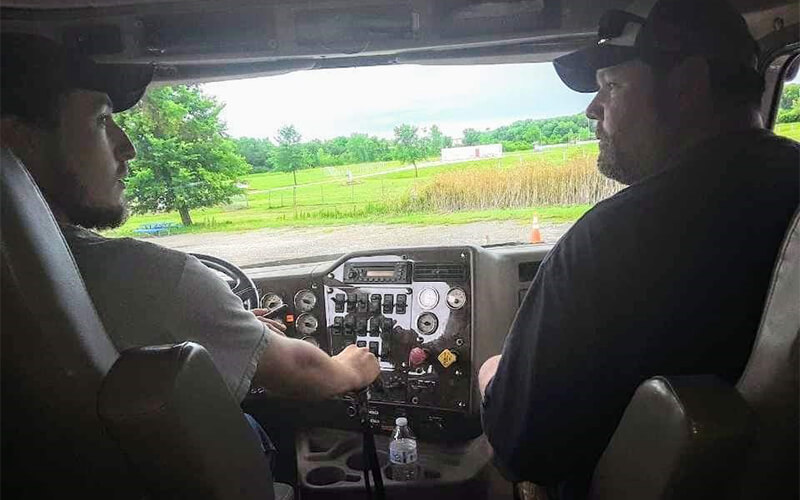 Father teaching son how to drive a semi truck