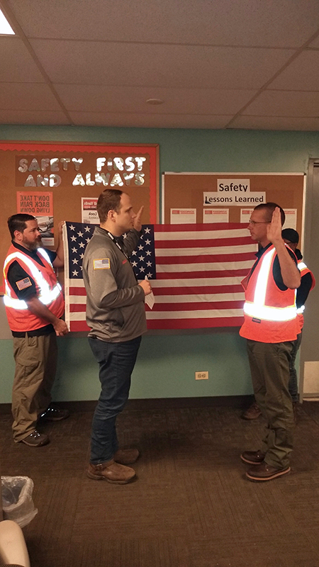 Operations Manager Corey Dyke performs the reenlistment ceremony for Intermodal driver Don Antle.