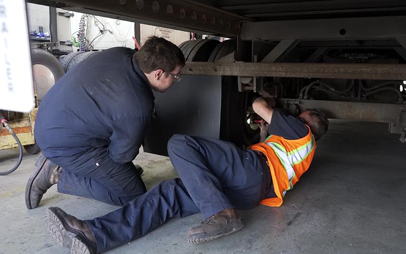 Two diesel mechanics work to fix a brake on a semi-truck.
