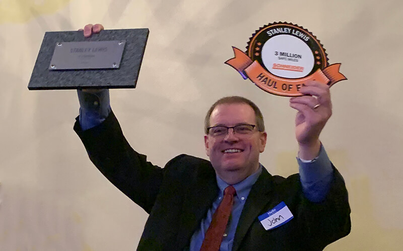 Truck driver shows Haul of Fame plaque from truck driver rewards and driver loyalty program