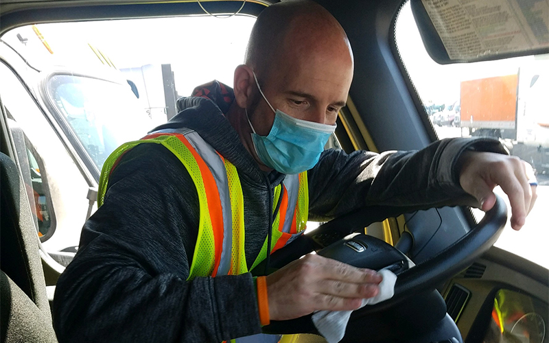 Truck driver with mask cleaning his truck.