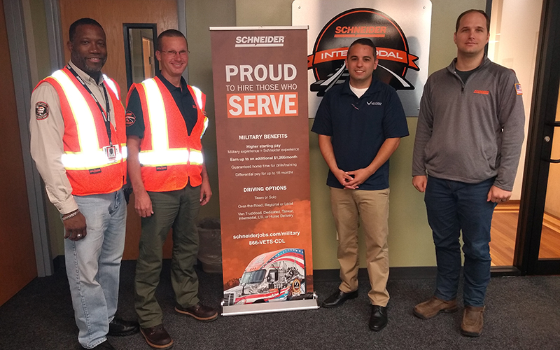 Intermodal driver Don Antle, Operations Manager Corey Dyke and Senior Instructor Willie Henderson stand by a Schneider military recruitment poster.