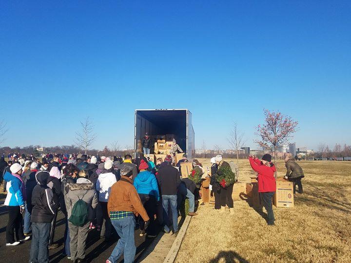 Volunteers unload wreaths off of trailer for Wreaths Across America